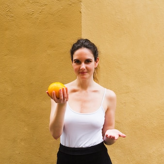 Medium shot woman holding an orange