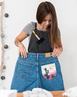 Donna del colpo medio che tiene i pantaloncini dipinti