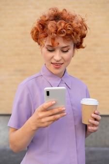 Donna del colpo medio che tiene telefono e caffè