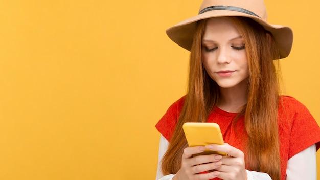 Средний выстрел женщина держит телефон