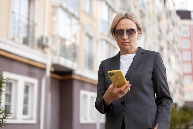Средний выстрел женщина, держащая телефон