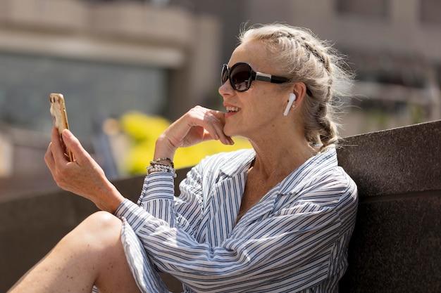 Donna con colpo medio che tiene il telefono