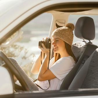 Средний снимок женщины, держащей фотоаппарат