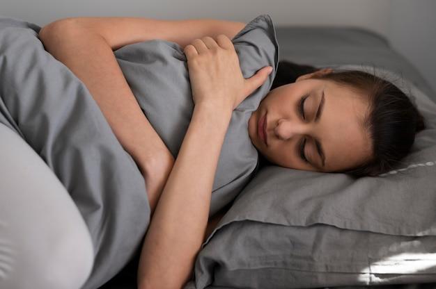 Средний выстрел женщина, держащая подушку