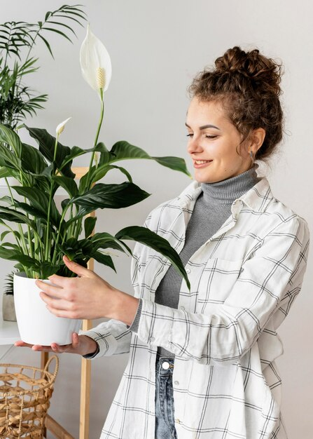 Medium shot woman holding plant pot
