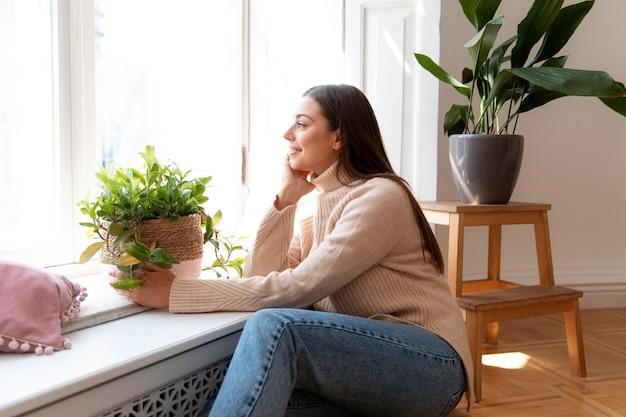 Donna del colpo medio che tiene il vaso della pianta