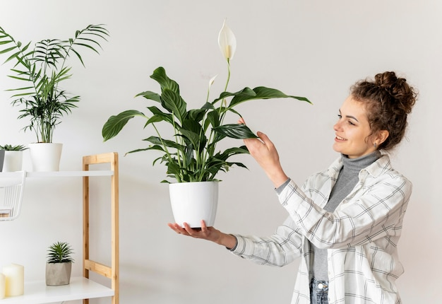 Medium shot woman holding plant
