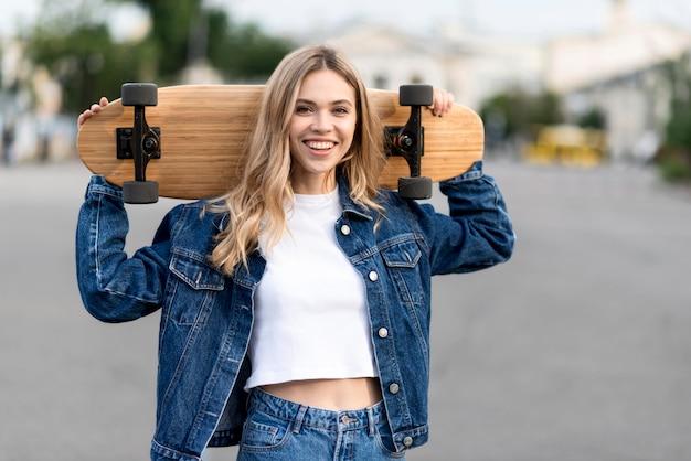 Colpo medio di donna che tiene uno skateboard