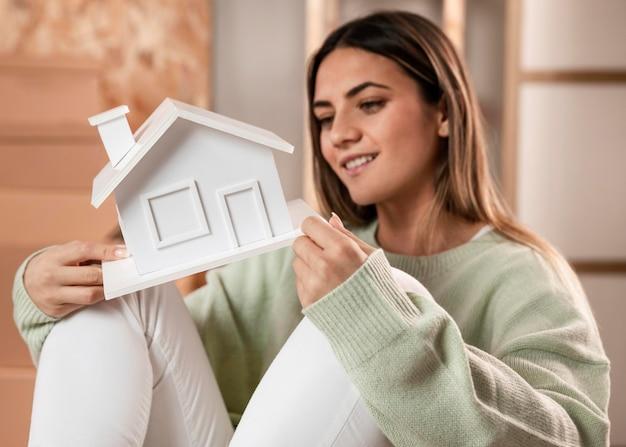 Medium shot woman holding small house