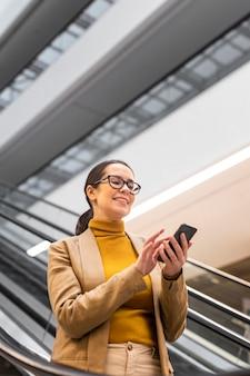 Medium shot woman holding smartphone