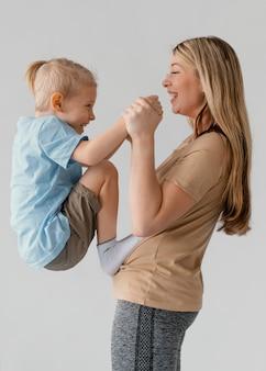 웃는 아이 들고 중간 샷 여자