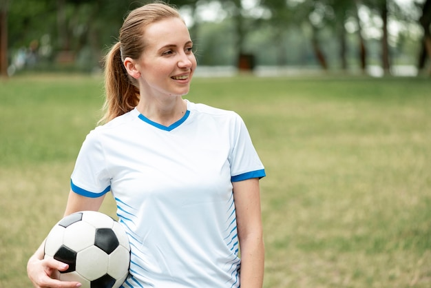 Средний выстрел женщина, держащая футбольный мяч