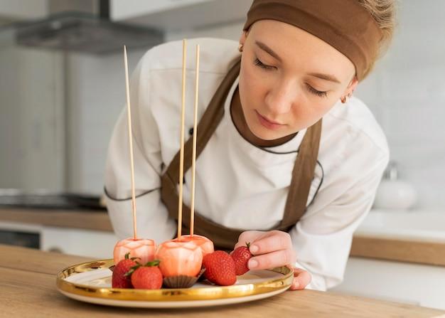 イチゴを持っているミディアムショットの女性