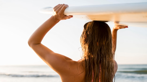 Medium shot woman holding surf board