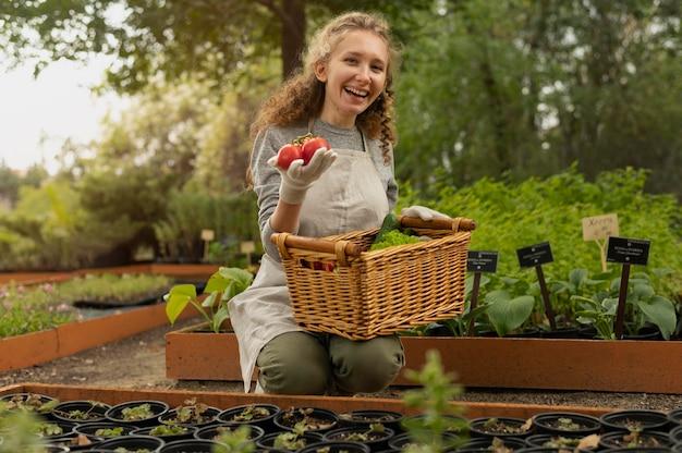토마토를 들고 중간 샷 여자