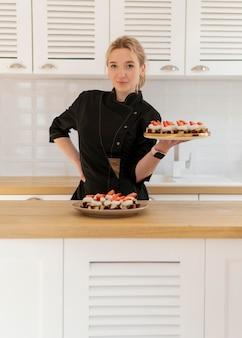 Medium shot woman holding tray with dessert