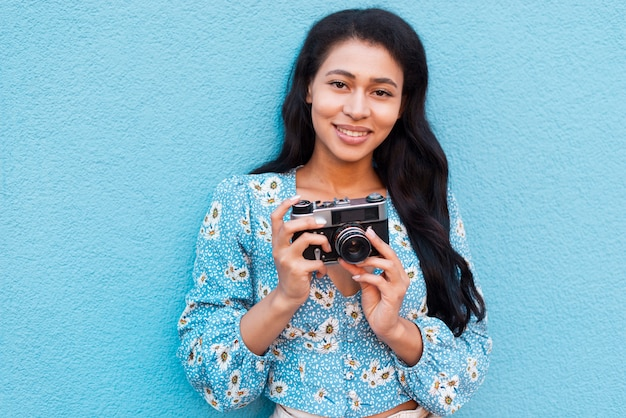 Medium shot of woman holding a vintage camera