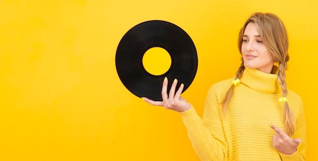 Medium shot woman holding vinyl