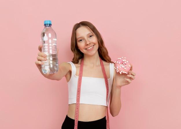Среднего выстрела женщина, держащая бутылку с водой