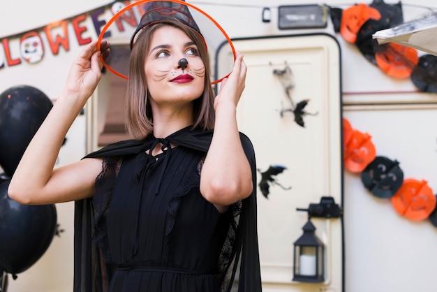 Medium shot woman holding witch hat