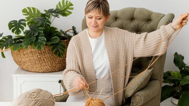 糸を保持しているミディアムショットの女性