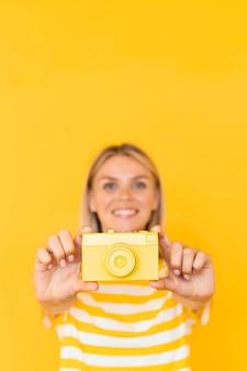 黄色のカメラを保持しているミディアムショットの女性