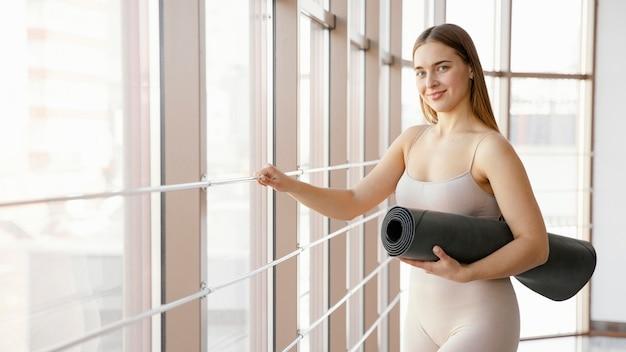 Женщина среднего размера, держащая коврик для йоги