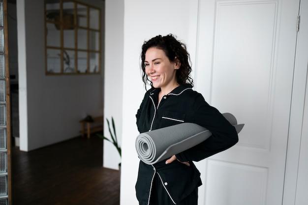 Среднего выстрела женщина, держащая коврик для йоги