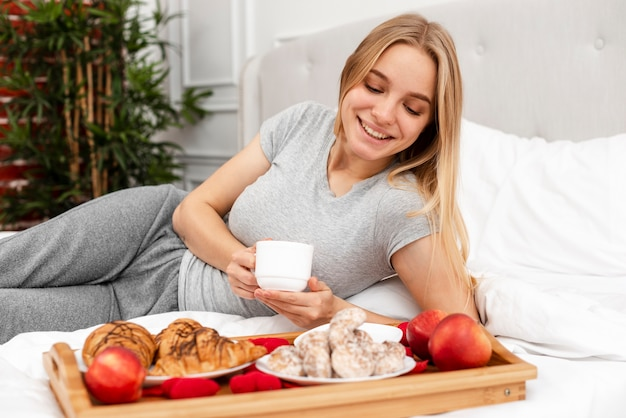 朝食付きのベッドでミディアムショットの女性