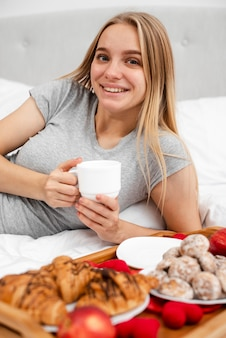 一杯のコーヒーとベッドでミディアムショットの女性