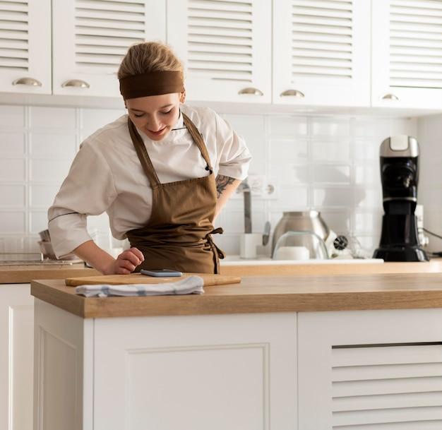 キッチンでミディアムショットの女性