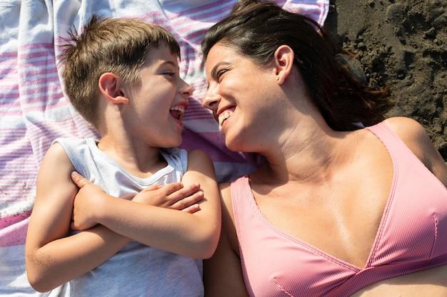 Medium shot woman and kid at beach