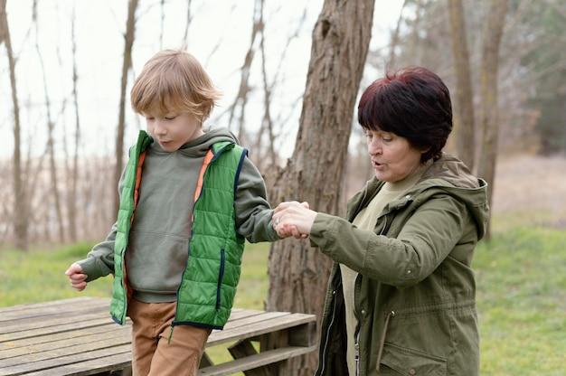 Medium shot woman and kid holding hands