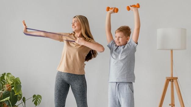 Medium shot woman and kid with sport equipment