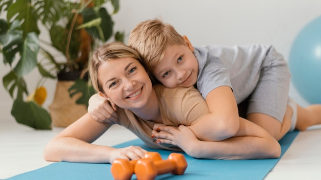 Medium shot woman and kid on yoga mat