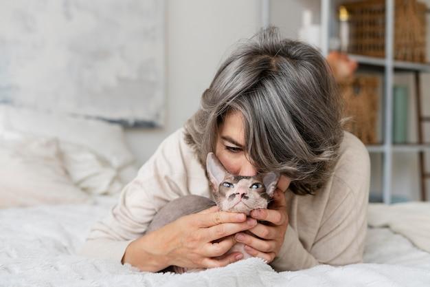 Medium shot woman kissing cat