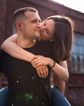 Medium shot woman kissing man on cheek