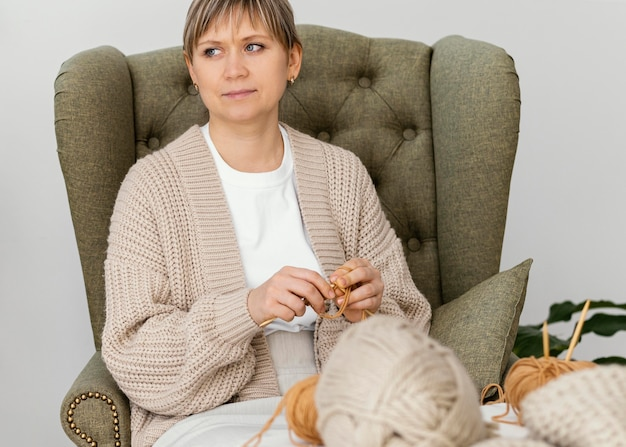 ミディアムショットの女性が編み物をして目をそらしている