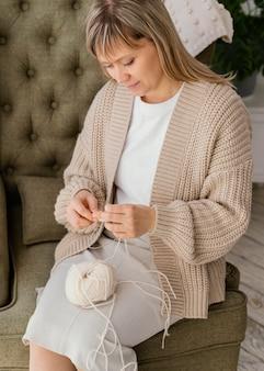 Colpo medio donna che lavora a maglia alto angolo