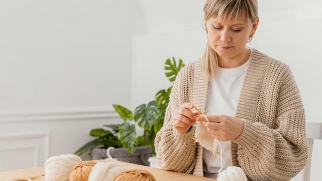 Donna del colpo medio che lavora a maglia a casa
