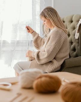 Donna del colpo medio che lavora a maglia all'interno