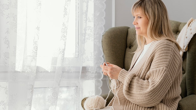 Donna del colpo medio che lavora a maglia vicino alla finestra
