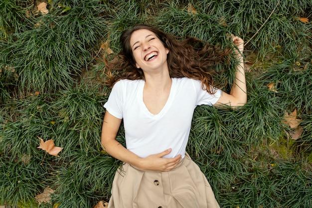 草の上で笑っているミディアムショットの女性