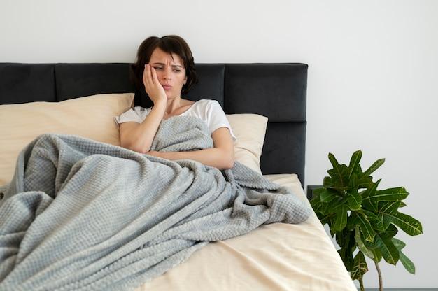 Colpo medio donna sdraiata a letto