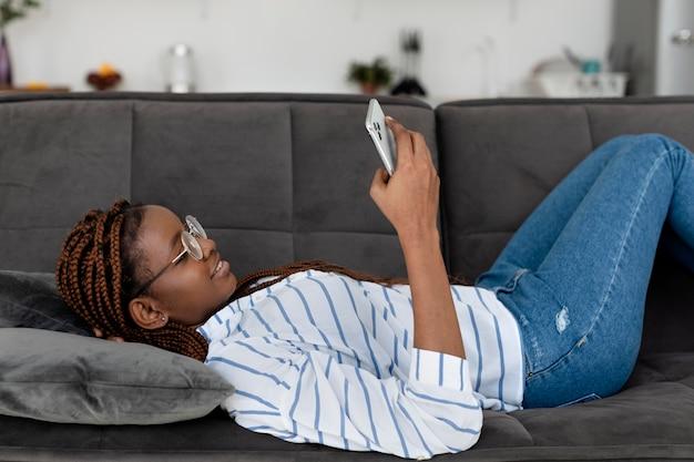 Colpo medio donna sdraiata sul divano