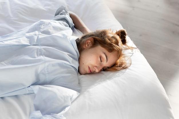 ベッドに横たわっているミディアムショットの女性