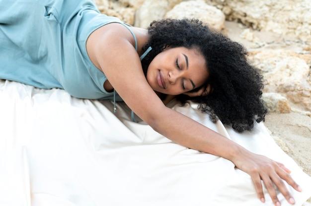 岩の上に横たわるミディアムショットの女性