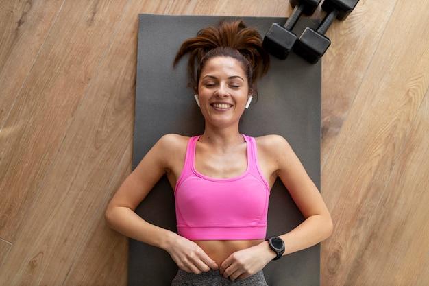 Женщина среднего размера, лежа на коврике для йоги