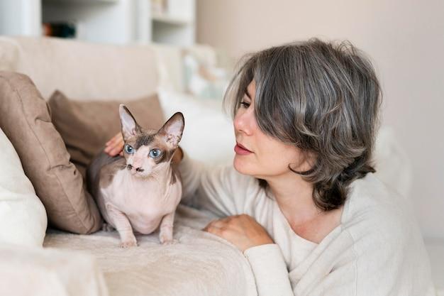 Женщина среднего выстрела, смотрящая на кошку