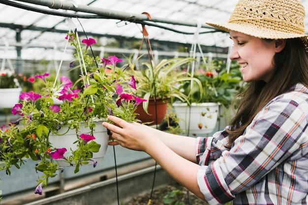 ミディアムショットの女性が花を見て